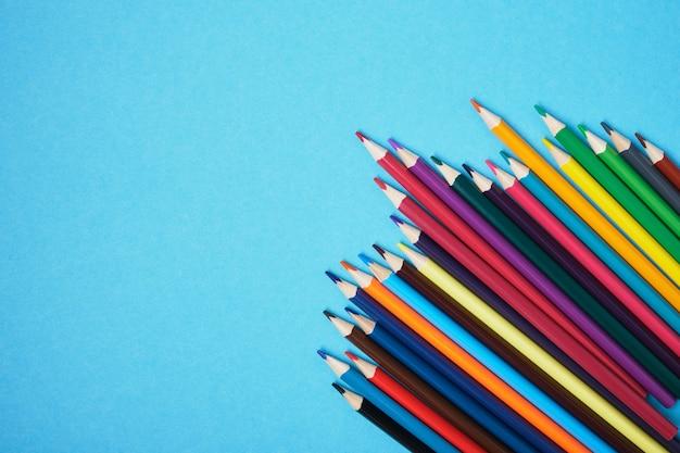 Kleurpotloden op een blauwe achtergrond met kopie ruimte