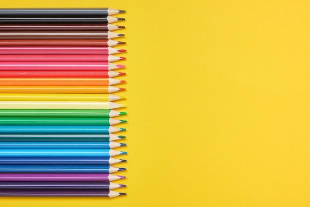 Kleurpotloden op een gele achtergrond met kopie ruimte