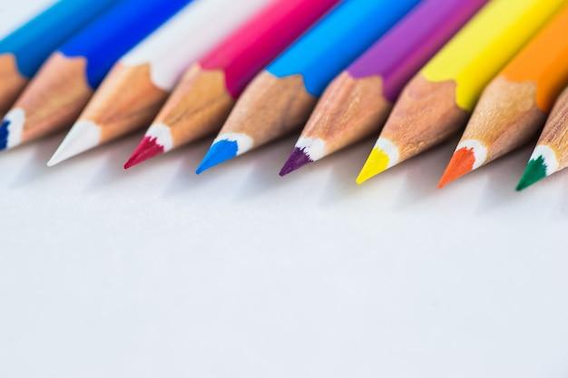 Kleurpotloden op een pastelkleurachtergrond aan een punt met ruimte voor tekst.