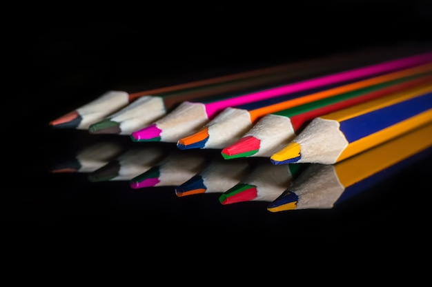 Kleurpotloden op een reflecterend glazen spiegeloppervlak. potloden met dubbele kleur op zwarte geïsoleerde achtergrond.