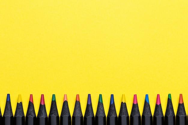 Kleurpotloden op een rij op geel