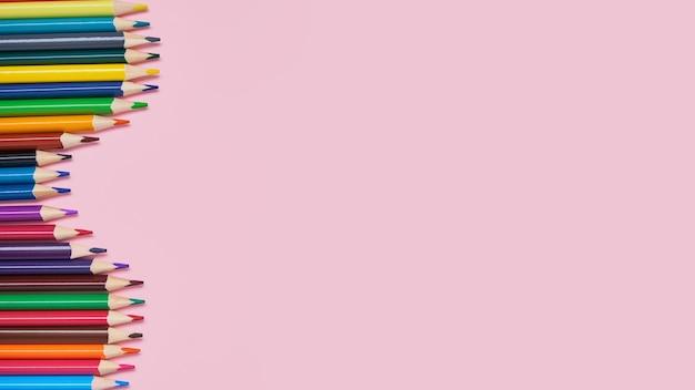 Kleurpotloden op een roze achtergrond met kopie ruimte
