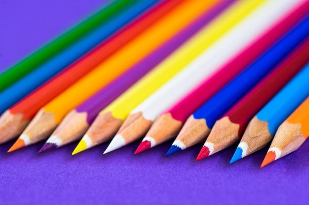 Kleurpotloden op een violette achtergrond met ruimte voor tekst.