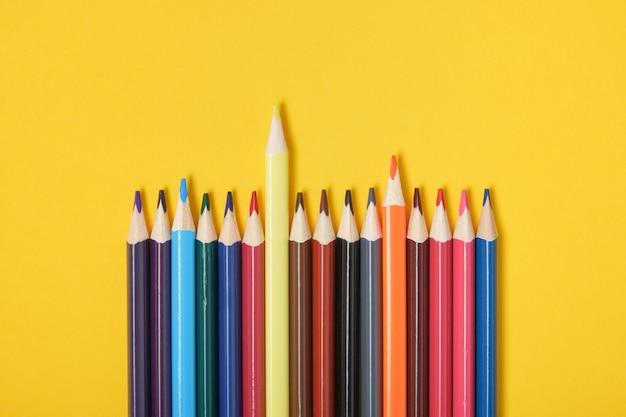 Kleurpotloden op gele achtergrond bovenaanzicht een potlood valt op