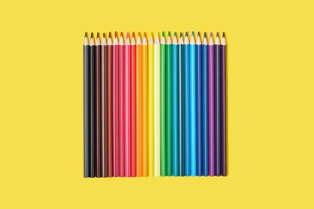 Kleurpotloden op gele achtergrond bovenaanzicht kopie ruimte