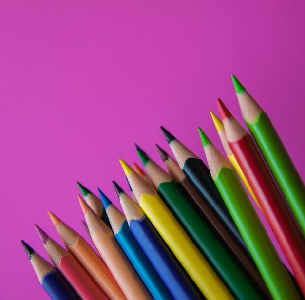 Kleurpotloden op het roze oppervlak. detailopname.