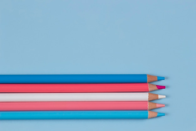 Kleurpotloden op lichtblauwe achtergrond pastel roze blauw witte kleuren bovenaanzicht
