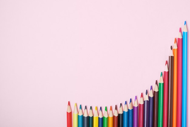 Kleurpotloden op roze achtergrond bovenaanzicht kopie ruimte kleurpotloden zijn in de vorm van een grafiek