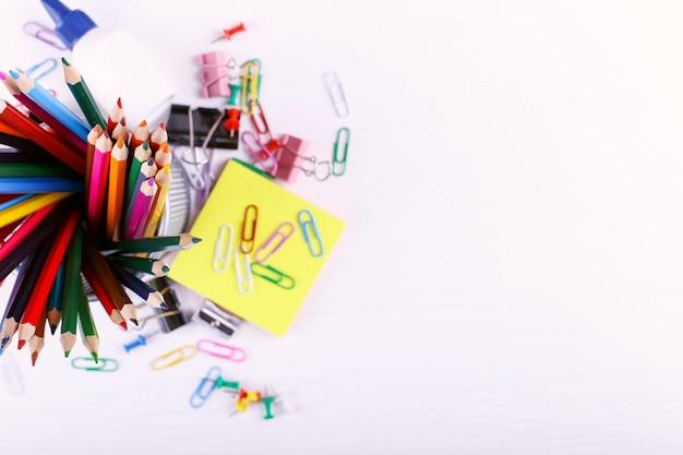 Kleurpotloden, paperclips en spelden, schoolbenodigdheden voor tekenen, kopie ruimte.