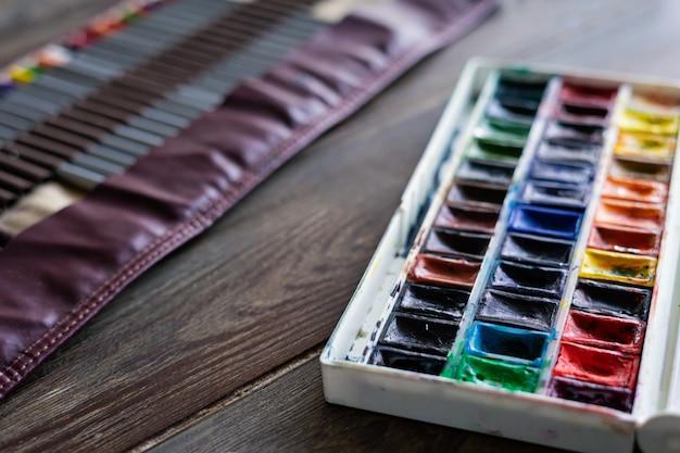 Kleurpotloden, penselen en aquarelverf