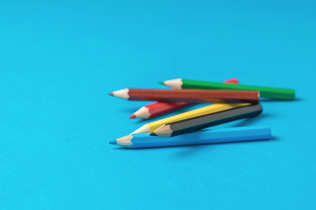 Kleurpotloden verspreid over een blauwe achtergrond. schrijfwaren en schoolbenodigdheden.