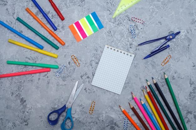 Kleurpotloden, viltstiften, stickers, blocnote, paperclips, schaar, liniaal en kompassen liggen op een grijze
