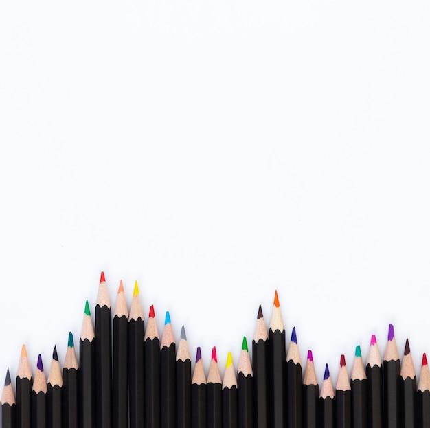 Kleurpotloden voor het tekenen van gevouwen golfbodem, vrije ruimte voor tekst, witte achtergrond