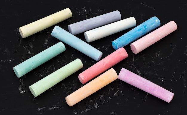 Kleurpotloden worden op een zwarte tekentafel voor kinderen gelegd.