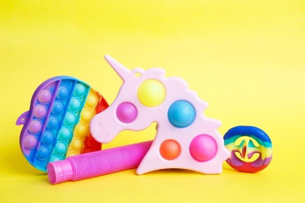 Kleurrijk antistress zintuiglijk fidgetspeelgoed op een gele achtergrond
