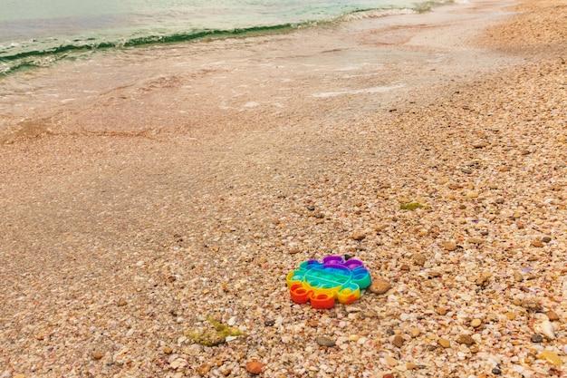 Kleurrijk antistress zintuiglijk pop-it-speelgoed op zand met water op het strand. zomer en ontspannen concept. autisme heeft siliconen speelgoed voor stressverlichting nodig