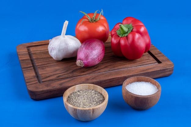 Kleurrijk assortiment van verse rijpe groenten op een houten bord met zout