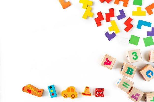 Kleurrijk babyspeelgoed op witte achtergrond. frame van het ontwikkelen van houten blokken, auto's en puzzels. natuurlijk, milieuvriendelijk speelgoed voor kinderen. bovenaanzicht plat leggen. kopieer ruimte.