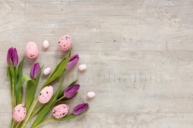 Kleurrijk beschilderde eieren voor pasen naast bloemen