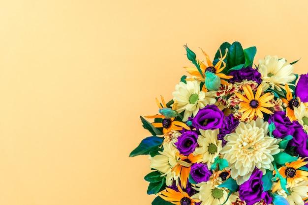 Kleurrijk boeket op lichtgele achtergrond. verse paarse en gele bloemen. kopieer ruimte