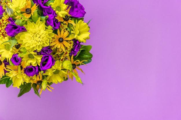 Kleurrijk boeket op lichtpaarse achtergrond. verse paarse en gele bloemen. kopieer ruimte