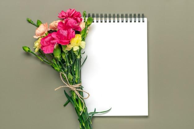 Kleurrijk boeket van verschillende roze anjer bloemen wit notitieboekje op groene achtergrond