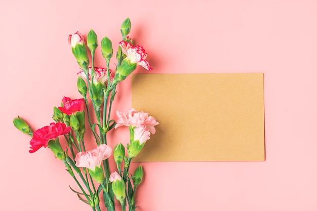 Kleurrijk boeket van verschillende roze anjerbloemen, wit notitieboekje op roze achtergrond