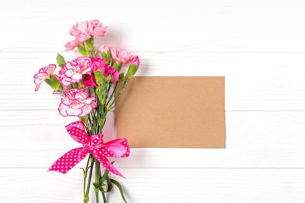 Kleurrijk boeket van verschillende roze anjerbloemen, wit notitieboekje op witte houten achtergrond
