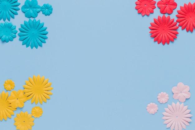 Kleurrijk decoratief bloemknipsel bij de hoek van blauwe achtergrond