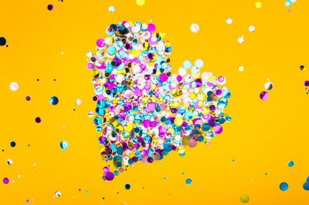 Kleurrijk die hart van confettien op gele achtergrond wordt gemaakt