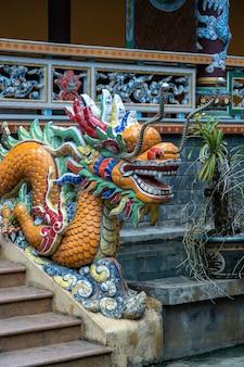 Kleurrijk draakbeeldhouwwerk bij de ingang van een boeddhistische tempel op de treden in de stad van danang
