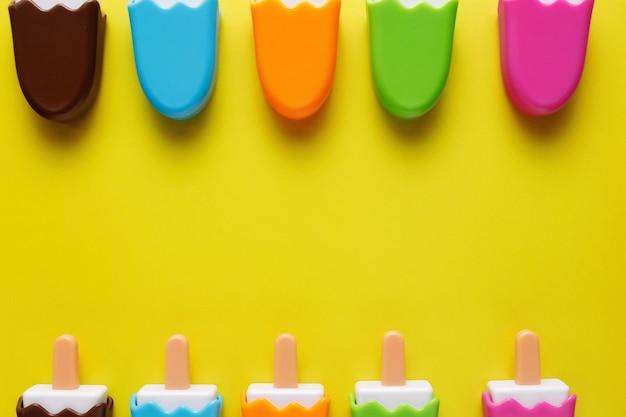 Kleurrijk en divers plastic speelgoed ijs met nummers voor baby's op een gele achtergrond.