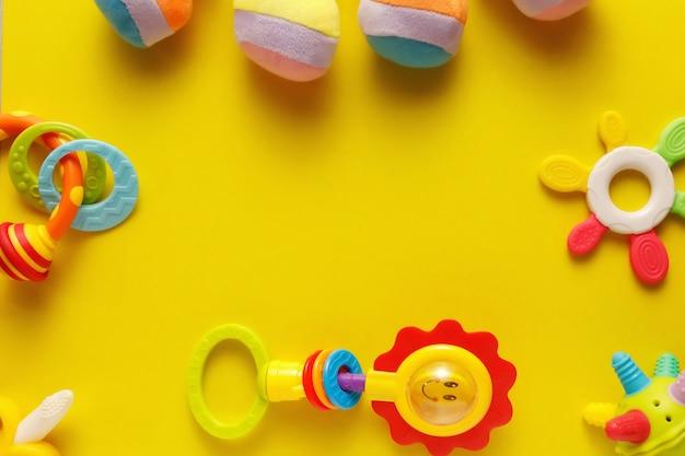 Kleurrijk en divers plastic speelgoed voor baby's op een gele achtergrond.
