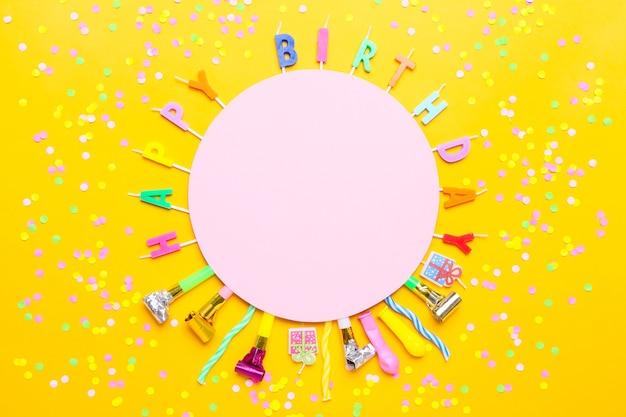 Kleurrijk feest met verschillende partijconfetti, ballonnen, kaarsen en decoratie op geel.