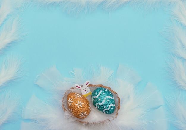 Kleurrijk geschilderde oranje en blauwe paaseieren met pasen konijn in mand met witte veren als een nest op blauw met veren