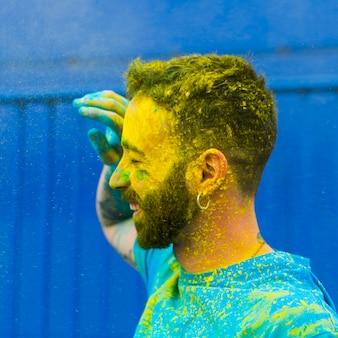 Kleurrijk gezicht van de gelukkige mens op holi-festival