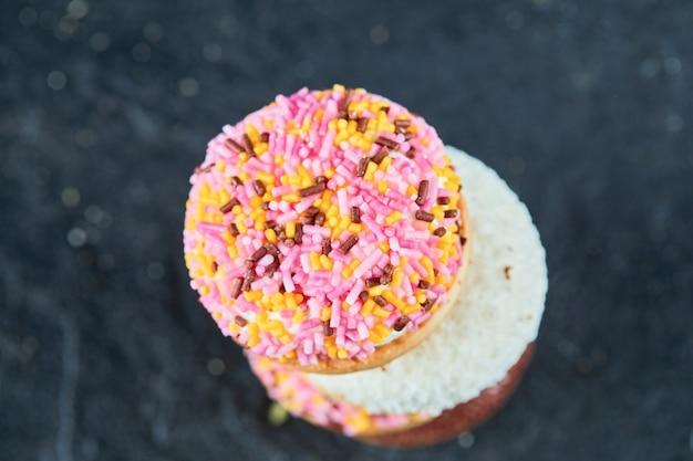 Kleurrijk gezwollen koekje op donkere ondergrond.