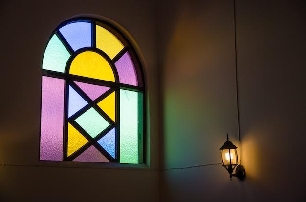 Kleurrijk glasvenster met lamplicht op muur