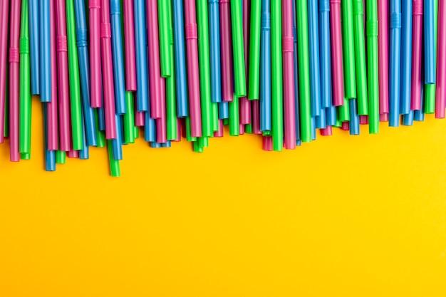 Kleurrijk het drinken stro op een gele achtergrond. ruimte voor tekst kopiëren.