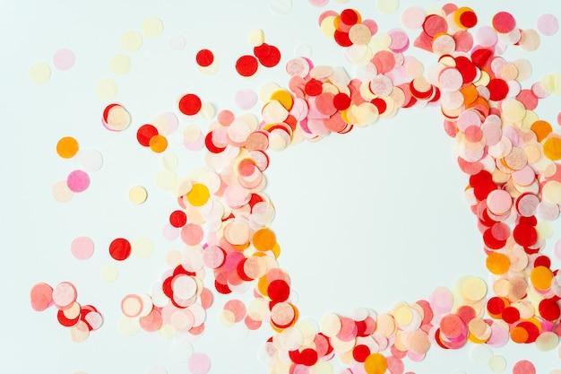 Kleurrijk kader dat met rode en oranje feestelijke confettien op pastelkleurachtergrond wordt gemaakt