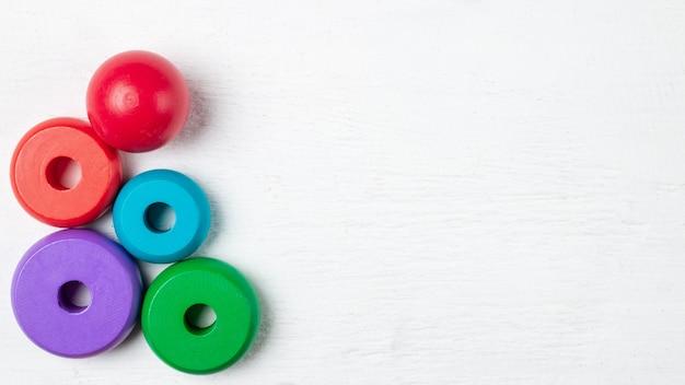 Kleurrijk kinderenspeelgoed op houten wit. bovenaanzicht. plat liggen. kopieer ruimte voor tekst