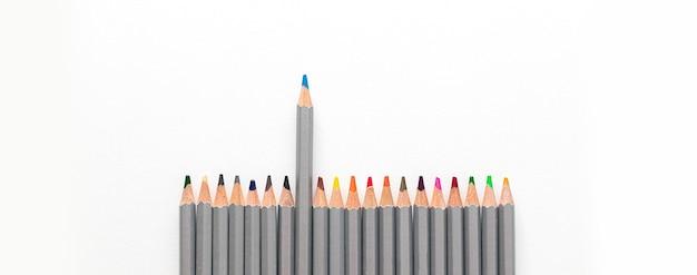 Kleurrijk kleurpotlood en wit papier op een witte tafelachtergrond