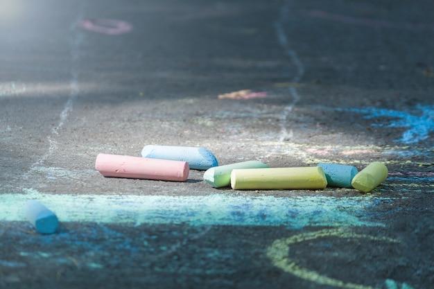 Kleurrijk krijt op het asfalt. tekenen met krijt op de stoep. veelkleurige kleurpotloden om te tekenen.