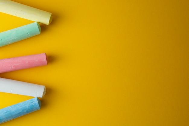 Kleurrijk krijt over gele achtergrond met exemplaarruimte.
