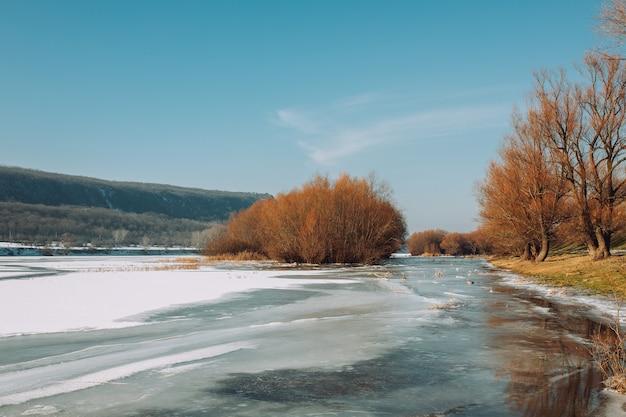 Kleurrijk landschap met bomen, rivier met sneeuw in koude zonnige dag