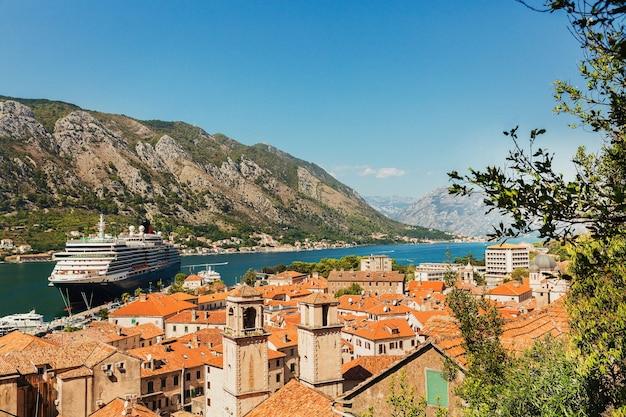 Kleurrijk landschap met oranje daken van de oude stad, boten en groot cruiseschip in jachthavenbaai, zee, bergen, blauwe hemel. bovenaanzicht van de baai van kotor, montenegro