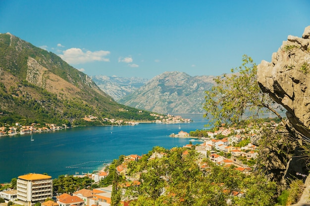 Kleurrijk landschap met oranje daken van de oude stad, boten en jachten in marina bay, zee, bergen, blauwe lucht. bovenaanzicht van de baai van kotor, montenegro