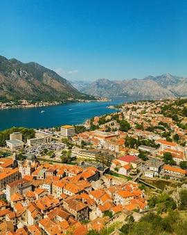 Kleurrijk landschap met oranje daken van de oude stad, boten en jachten in marina bay, zee, bergen, blauwe lucht