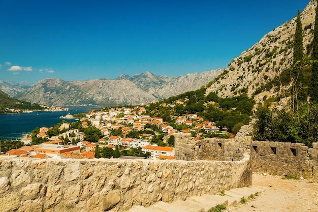 Kleurrijk landschap met oude muren in oude citadel, bergen, zee, blauwe hemel. bovenaanzicht van de baai van kotor van middeleeuwse vesting. historisch monument in montenegro
