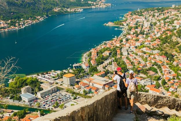 Kleurrijk landschap met oude muren in oude citadel, bergen, zee, blauwe lucht. bovenaanzicht van de baai van kotor van middeleeuwse vesting. historisch monument in montenegro